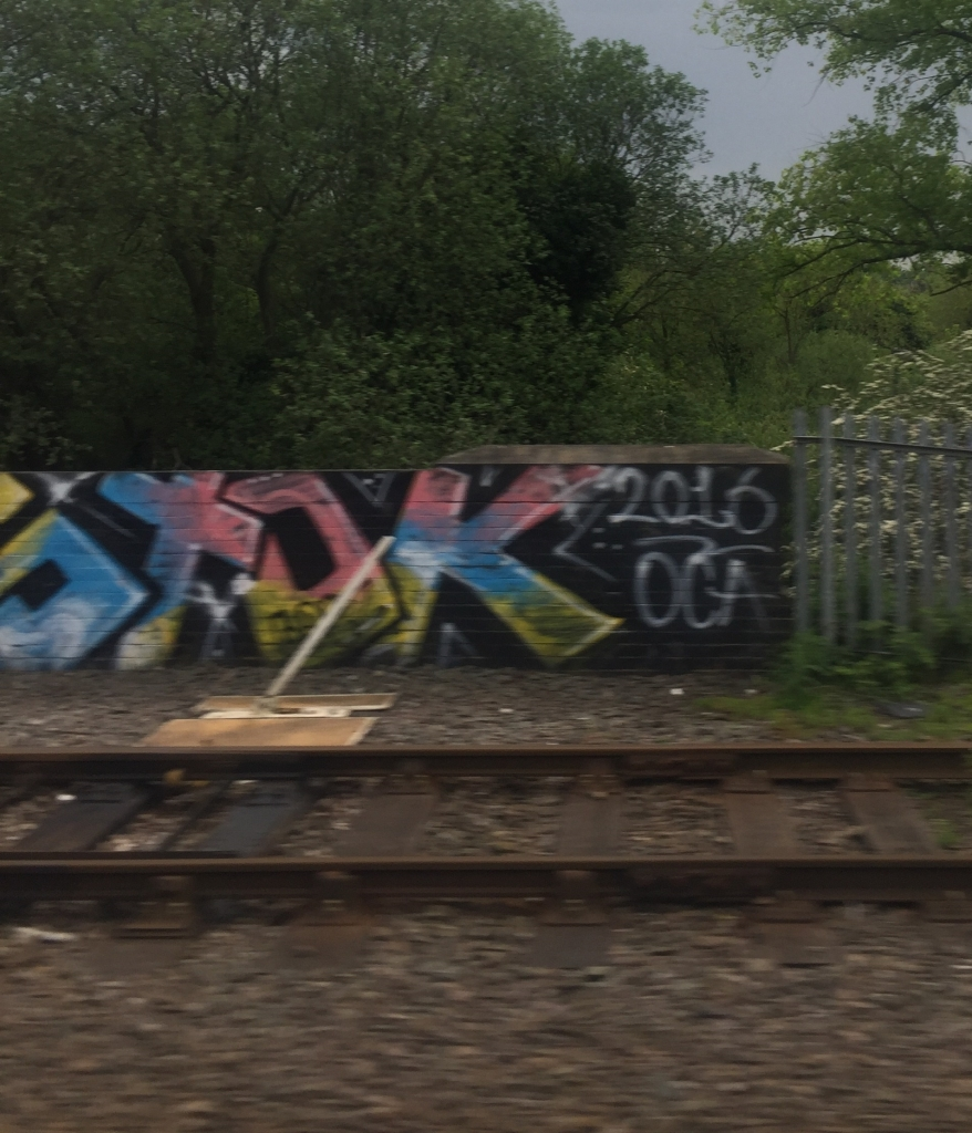 Grafitti covered wall by train tracks